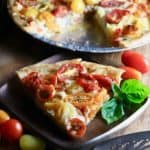 Southern Style Cherry Tomato Pie garnished with basil and cherry tomatoes in a white bowl on the side.