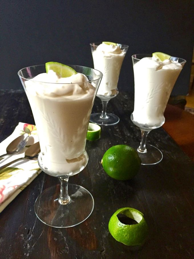 Three key lime mousses garnished with a lime wedge in parfait glasses.