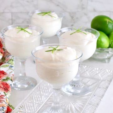 Four key lime mousses garnished with a lime wedge in parfait glasses.