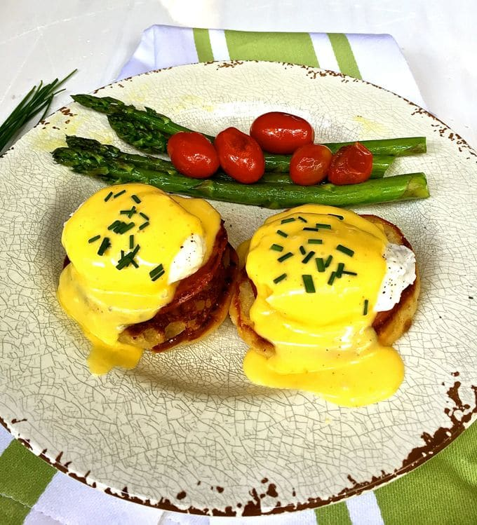 Eggs Benedict garnished with chives and asparagus and cherry tomatoes on the side.