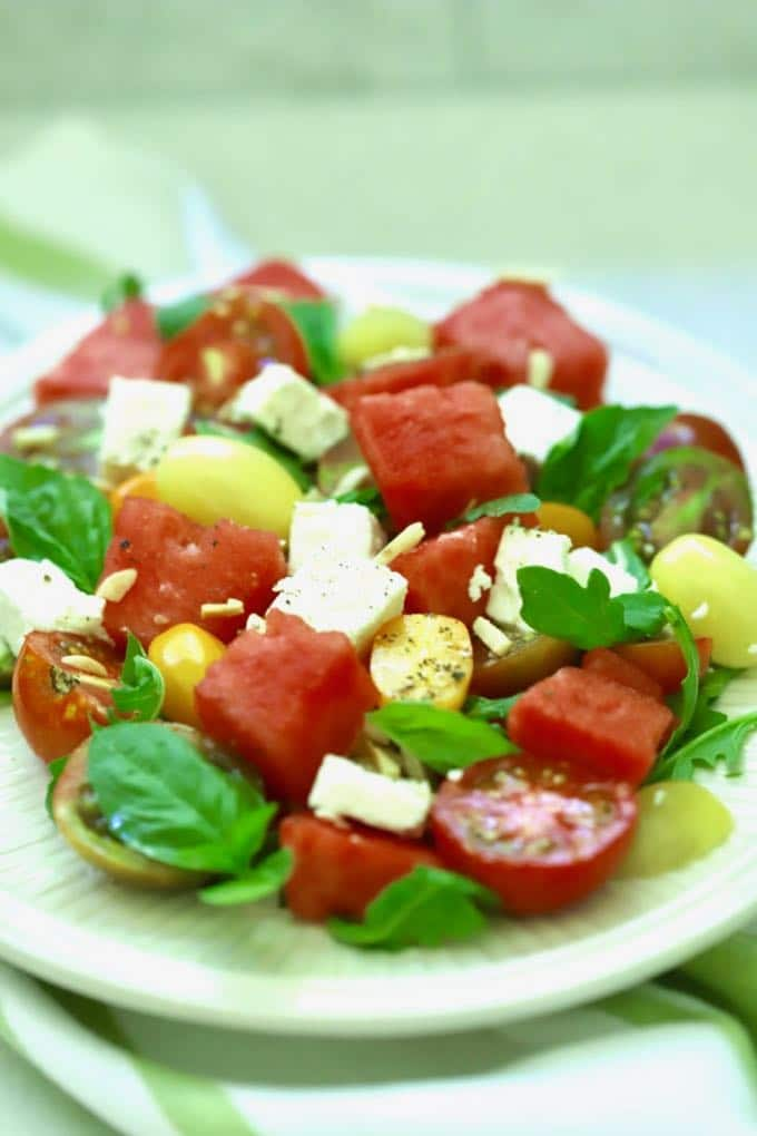 Southern Watermelon Tomato Salad on a white plate sitting on a green and white dish towl