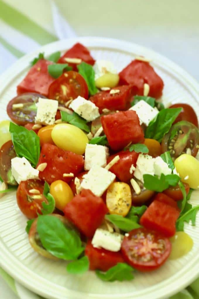 A large white plate filled with southern watermelon tomato salad garnished with feta cheese, slivered almonds, and chopped basil.