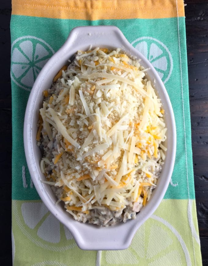 A casserole topped with shredded cheese and panko bread crumbs ready to bake.