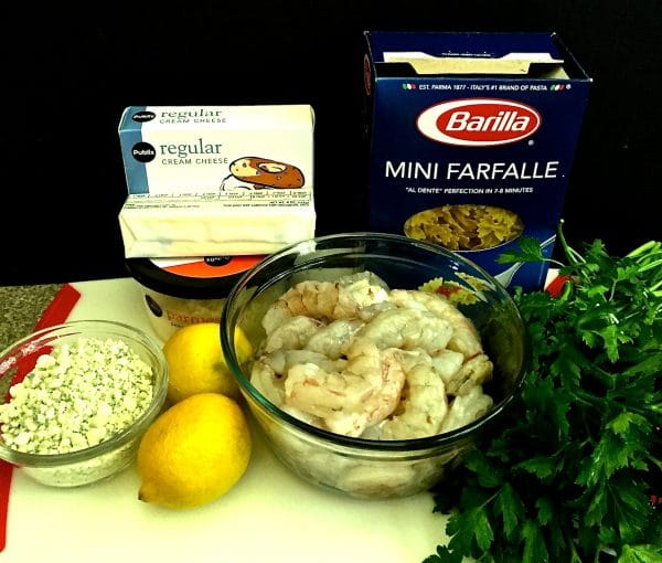 Shrimp and Blue Cheese Pasta ingredients on a cutting board including raw shrimp and bow tie pasta.