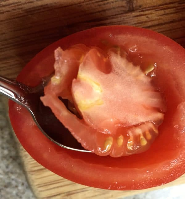 One sliced plum tomato with a spoon scooping out the tomato seeds and the center.