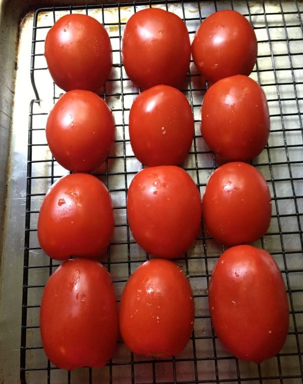 Tomatoes cut side down on a wire rack set over a baking sheet.
