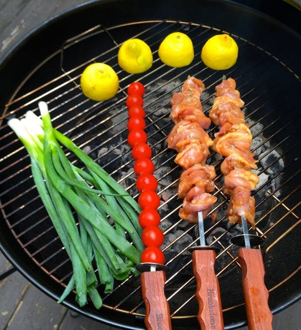 Chicken Skewers, cherry tomato skewer, scallions and lemons on a grill.