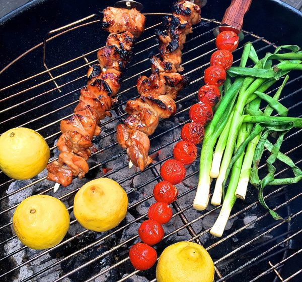 Grilled Chicken Skewers, cherry tomato skewer, scallions and lemons on a grill.