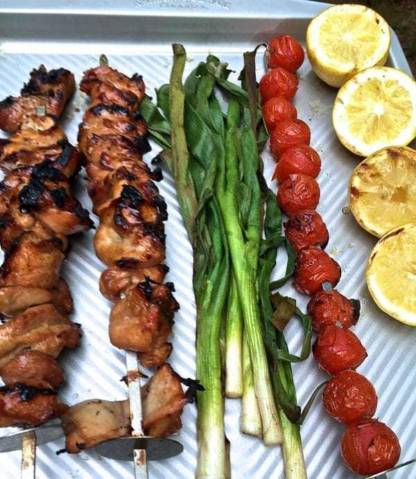 Grilled Chicken Skewers, cherry tomato skewer, scallions and lemons on a baking sheet.