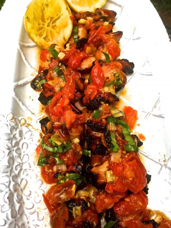 Grilled Chicken Skewers with Tomato Relish on a serving platter garnished with scallions and lemon.