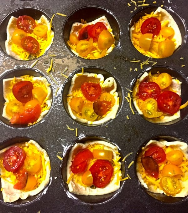 Puff pastry sheets, shredded cheese, and sliced heirloom tomatoes in a muffin pan.