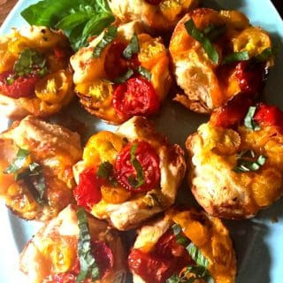 Muffin Pan Tomato Tarts with Puff Pastry on a plate garnished with basil.