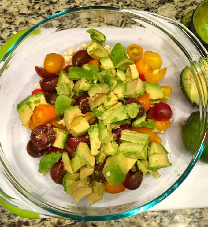 In a large glass bowl is sliced tomatoes and diced avocados on top of kernels of corn.