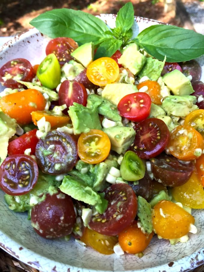 Corn, Tomato, and Avocado Salad garnished with basil in a white rustic bowl.