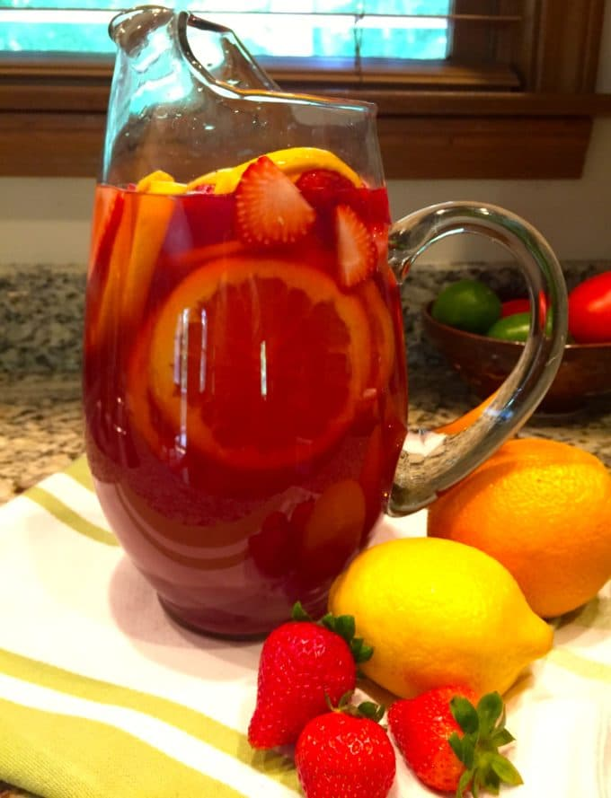 A tall glass pitcher of Summer Rose Sangria garnished with strawberries, lemons and oranges