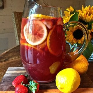 Summer Rose Sangria in a glass pitcher with orange and lemon slices and strawberries