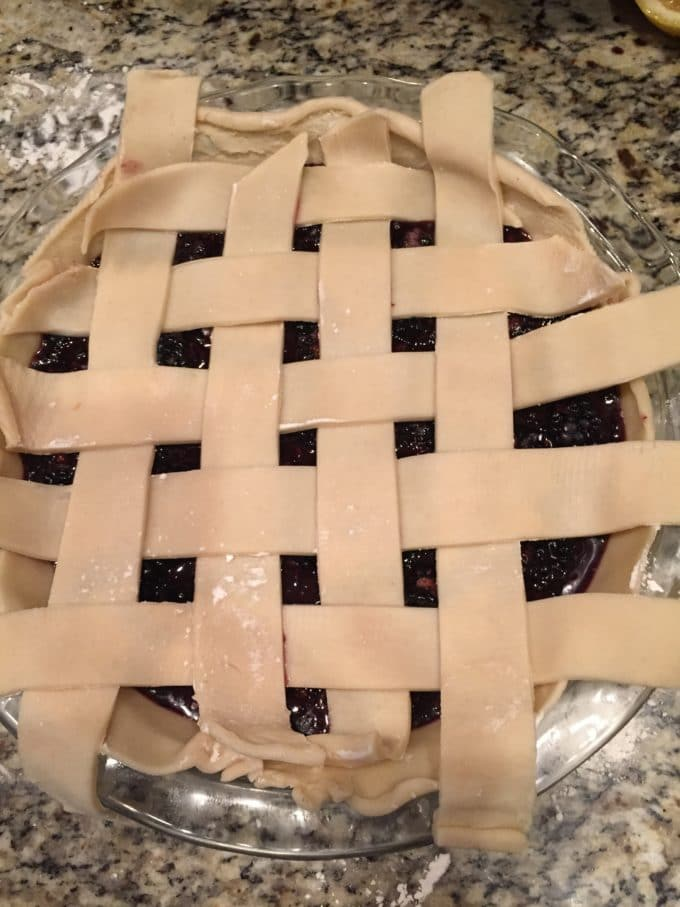 Arranging strips of pie dough to make a lattice crust.
