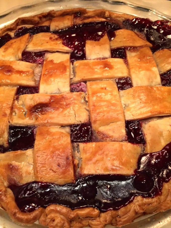 Blackberry pie with a golden-brown lattice crust in a glass pie dish.