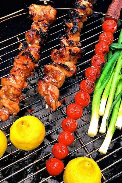 Perfect for your next BBQ, Grilled Chicken Skewers with Tomato Relish features marinated chicken kabobs topped with grilled tomatoes, scallions, and lemons!