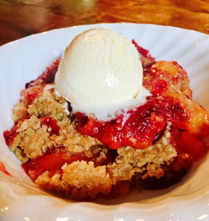 Homemade Peach and Blackberry Crumble topped with vanilla ice cream.