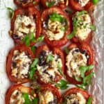 Roasted Tomatoes with Feta, Olives and Pine Nuts garnished with chopped basil on a serving plate.