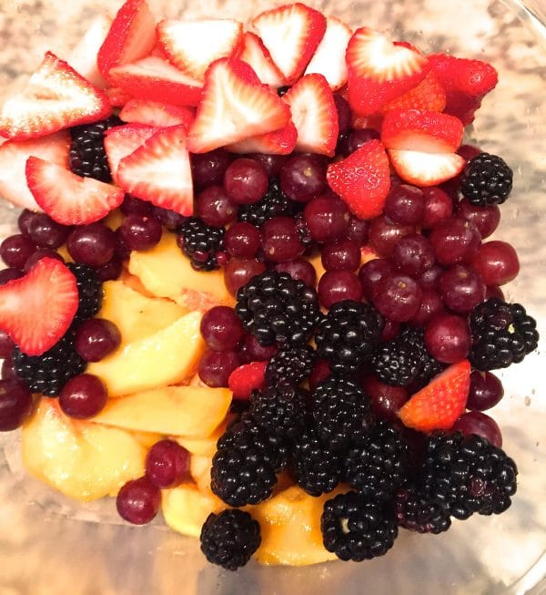 Sliced peaches, blackberries, grapes, and sliced strawberries in a large glass bowl.