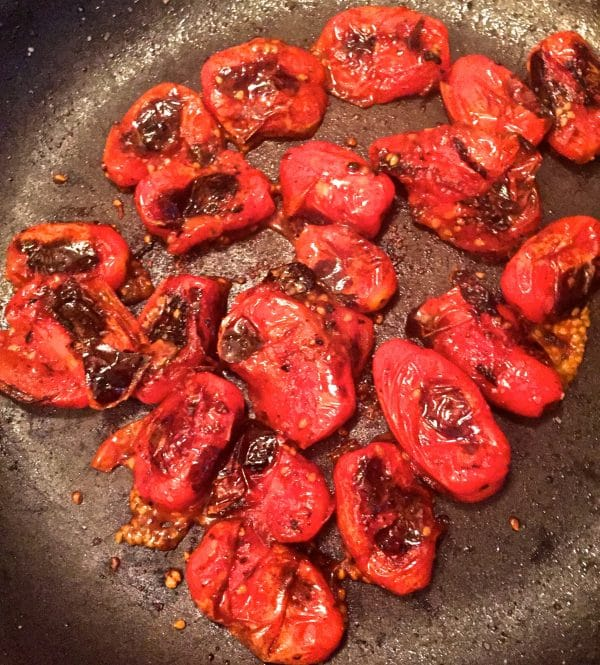 Cherry tomatoes and crushed red pepper flakes being sautéed in a heavy-duty skillet.