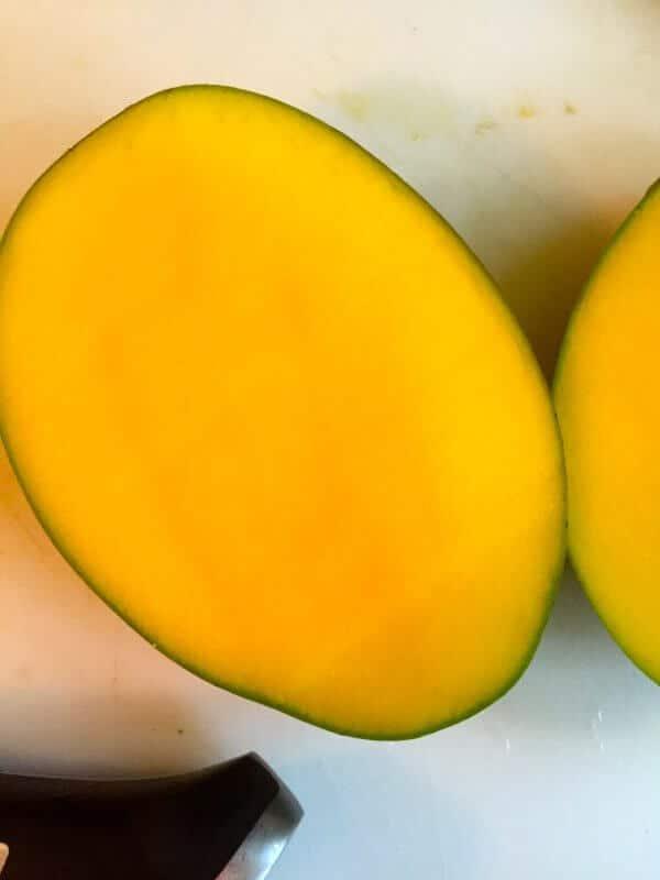 Two ovals of mango flesh on a cutting board.