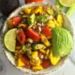 Spicy Quinoa and Mango Salad garnished with sliced avocado and a lime wedge in white rustic bowl.