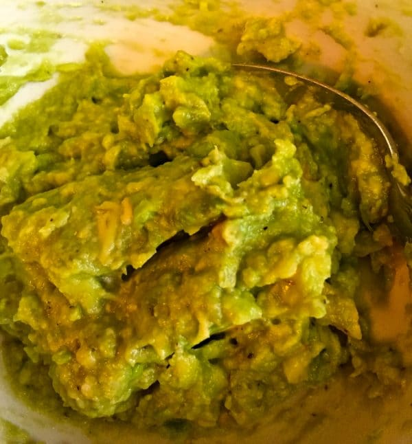 Mashed avocados in a medium size bowl with a spoon.