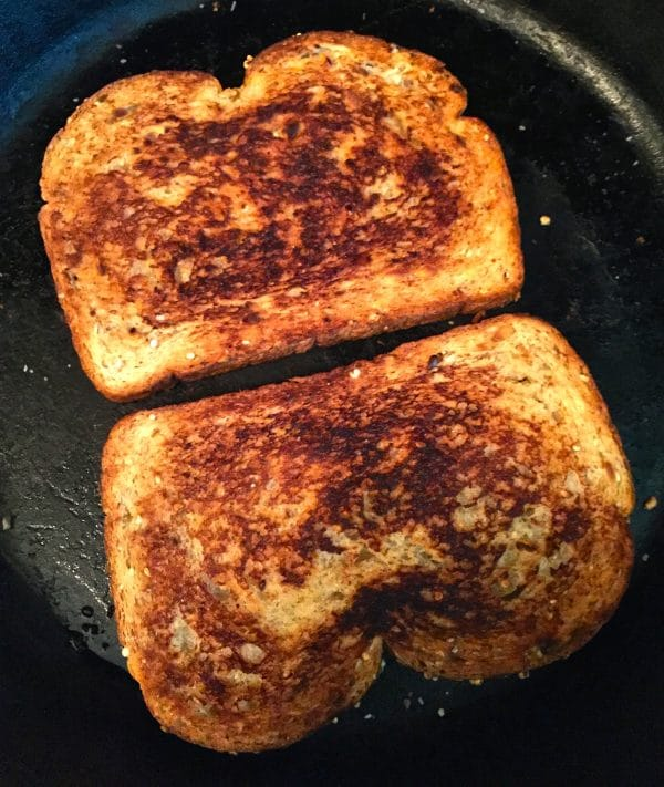 Two pieces of toast that are golden brown in a large skillet.