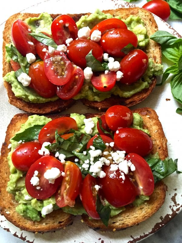 Bruschetta Avocado Toast with crumbled goat cheese and fresh basil for garnish.