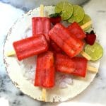 Strawberry Margarita Ice Pops on a white plate with ice, lime slices and strawberries