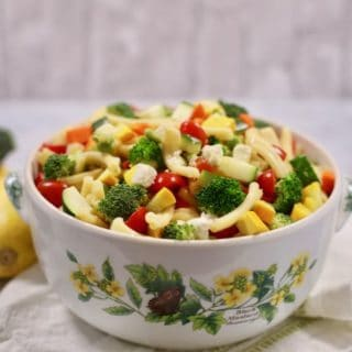 A large bowl with pasta salad and vegetables on a white and green napkin.
