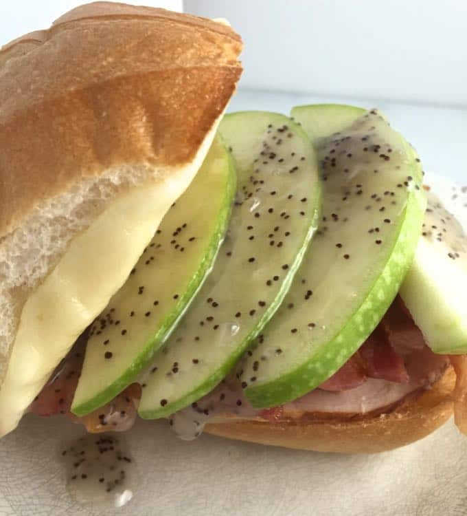 Chicken Club sandwich with sliced apples and poppyseed dressing.
