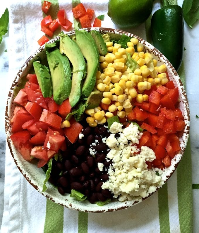 Mexican Chopped Salad with Honey Lime Dressing in a large bowl with black beans, cotija cheese, tomatoes and corn.