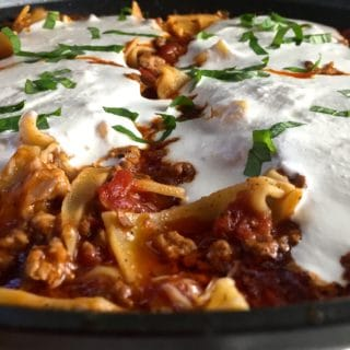 Skillet lasagna in a pan with melted ricotta cheese.