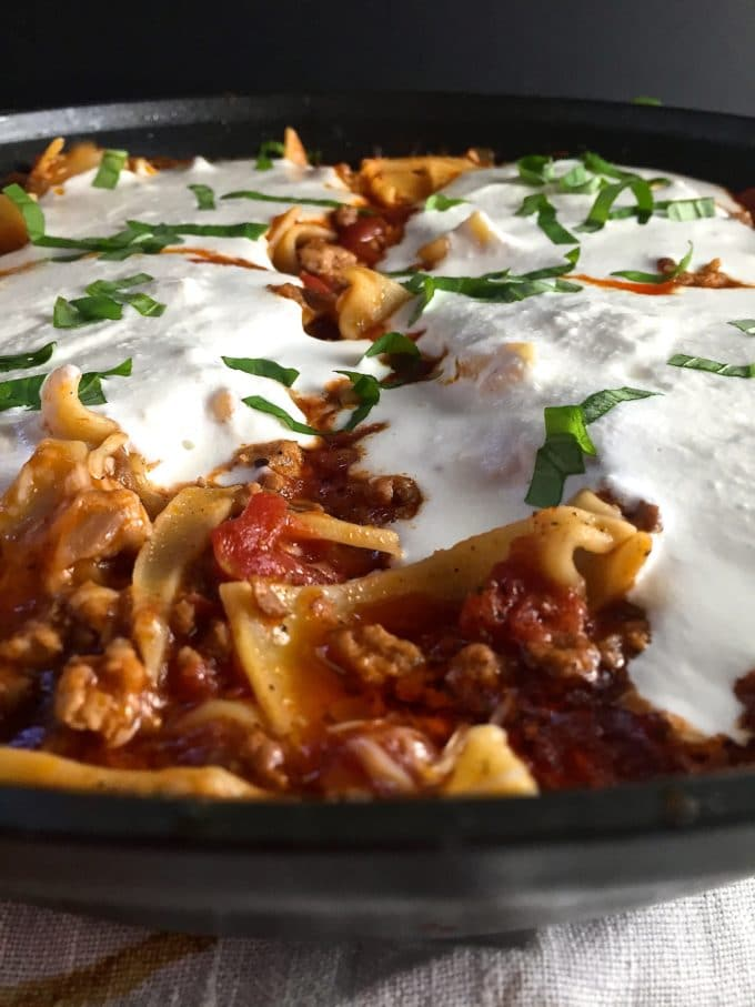 Skillet lasagna topped with melted ricotta cheese cooks in a skillet.