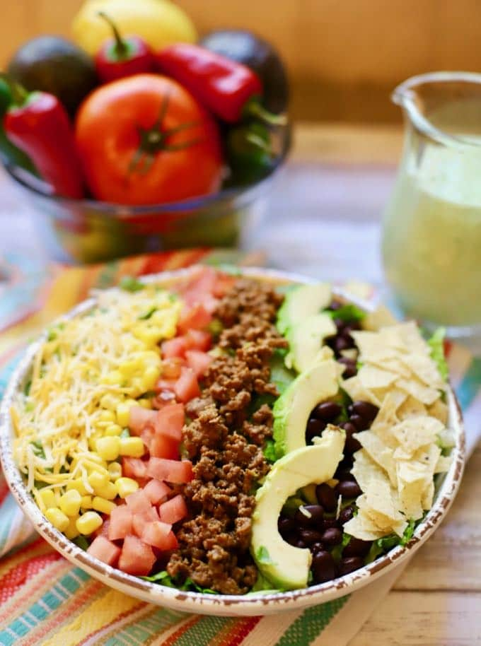 Beef Taco Salad with Avocado Lime Dressing ready to eat with a pitcher of dressing