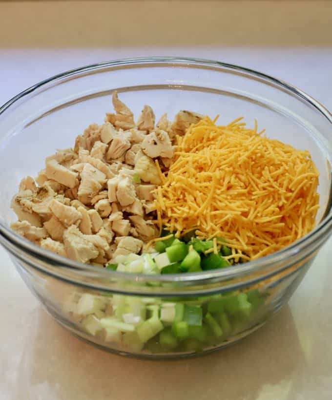 Chopped chicken, cheese and bell pepper in a clear glass bowl.