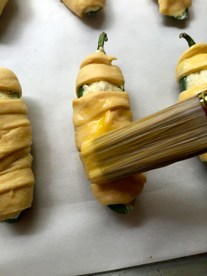 Easy Halloween Jalapeño Mummies brushing on egg wash before baking