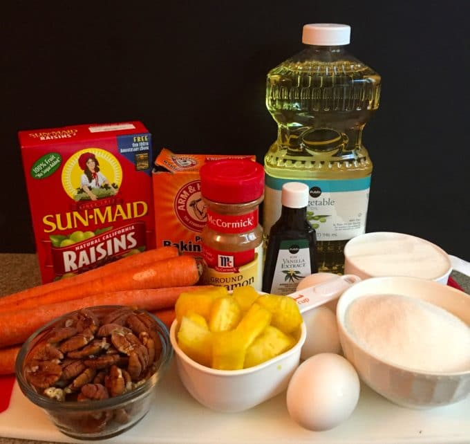 Easy Carrot Cake recipe ingredients including pecans, pineapple, oil, flour, egg, oil, raisins and carrots.