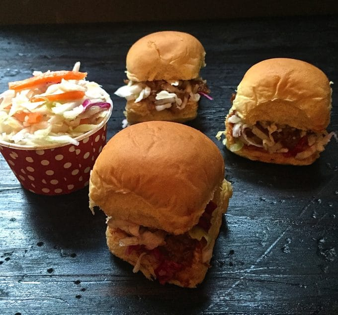 Pulled pork sliders with coleslaw on a wooden board.