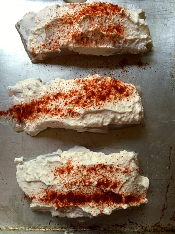 Grouper fillets topped with sour cream and paprika for Easy Baked Parmesan Grouper Fillets
