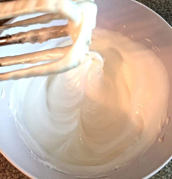 Using an electric mixer to make the meringue for Easy Halloween Meringue Ghosts.
