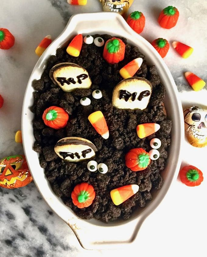 Halloween Graveyard Chocolate Cheesecake Dip in a bowl topped with candy and cookies.