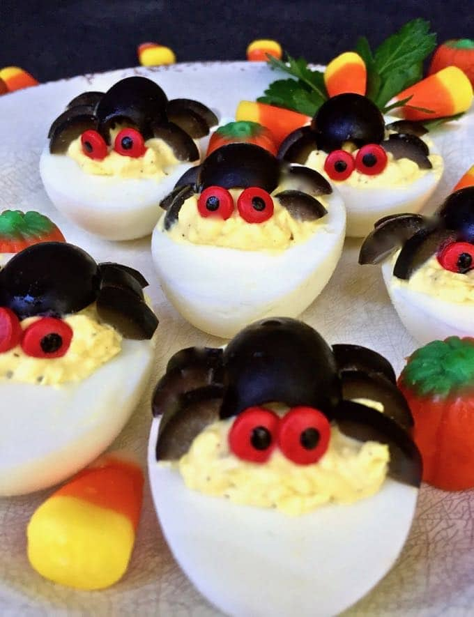 Halloween Spooky Spider Deviled Eggs on a plate with candy corn.