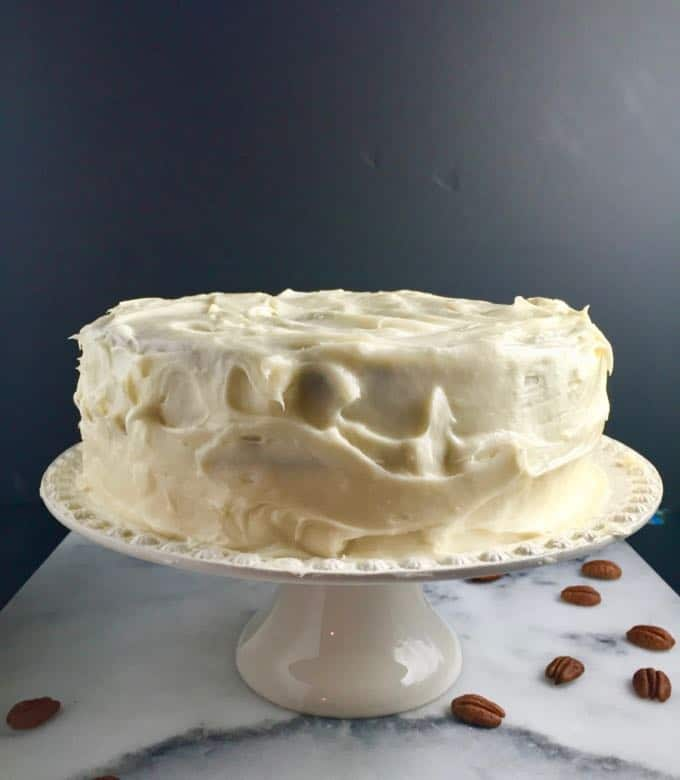 Easy Carrot Cake with Cream Cheese Icing on a platter with pecans scattered around the base