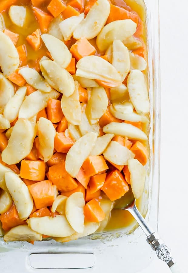 A clear glass baking dish with candied yams with apple slices.
