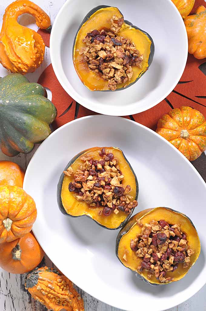 Cranberry and walnut stuffed acorn squash on a white plate.